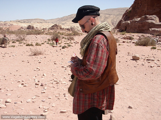 Photo of Wade of Vagabond Journey takes notes in the desert of Jordan