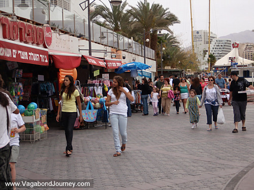 Israeli people walking on the Eilat boardwalk. Cost of travel in Eilat,
