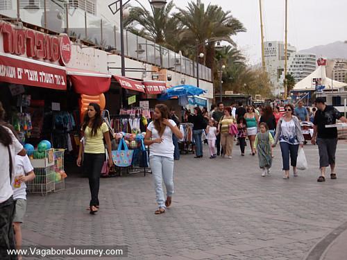 Israeli people walking on the Eilat boardwalk. Cost of travel in Eilat,