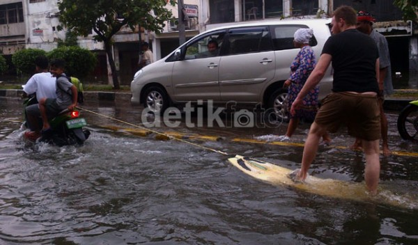 Foreigner surfing the flooded streets of Jakarta