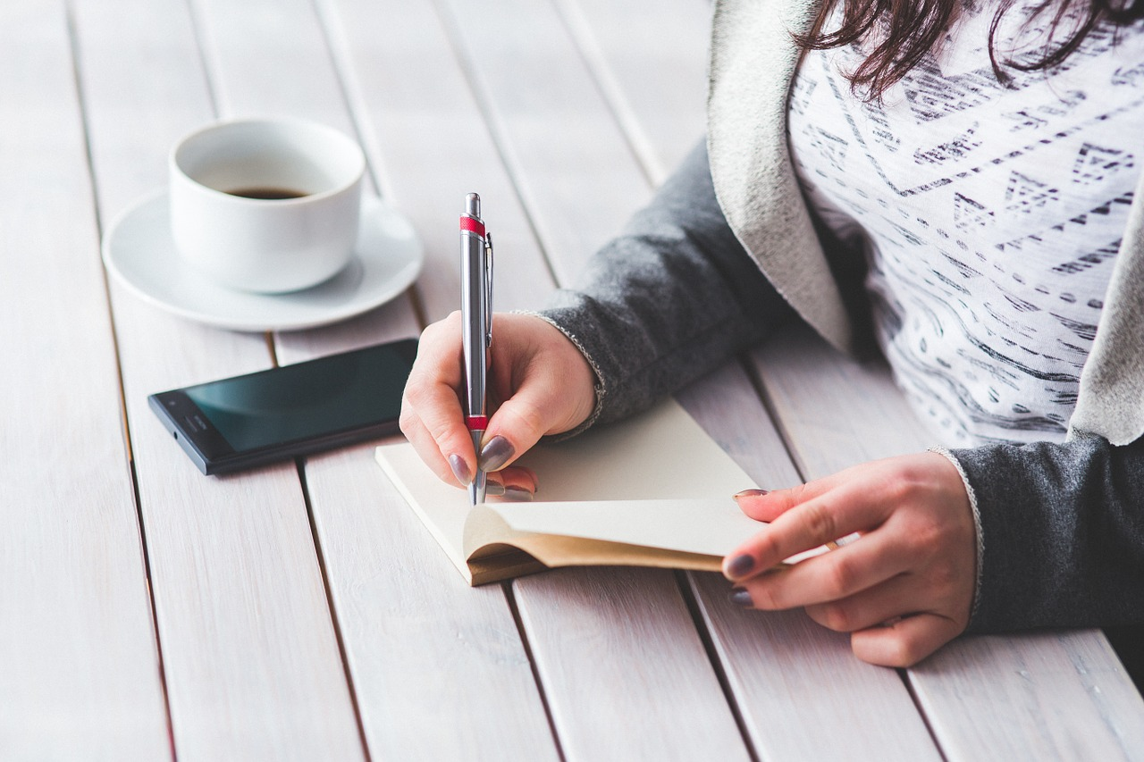 Lady writing on paper with coffee