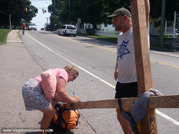 A woman signs Tom Helling's cross